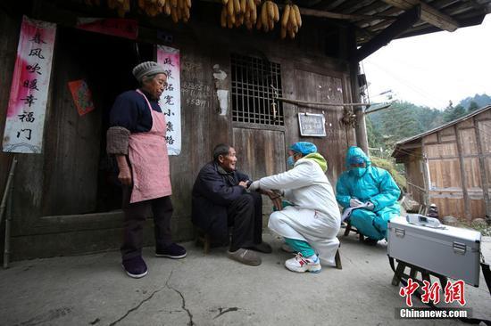 图为1月31日,肖世军(蓝衣)、潘启兰在为村民巡诊。 中新社发 黄晓海 摄