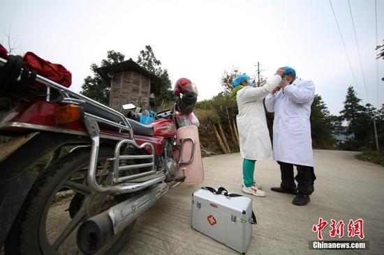图为1月31日,潘启兰(左)大发棋牌玩法帮助 肖世军整理防护帽。 中新社发 黄晓海 摄