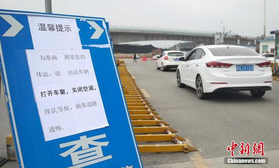 1月31日,在厦蓉高速贵阳东收费站出口,相关人员和车辆排队等待接受检测、登记,以防控新型冠状病毒感染的肺炎疫情。中新社记者 瞿宏伦 摄