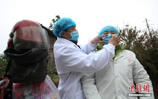 图为在大发棋牌玩法贵州 丹寨排调镇党早村宰飞自然寨,肖世军(左)在整理潘启兰的防护口罩。 黄晓海 摄