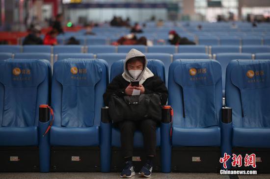 2月1日,受新型冠状病毒感染的肺炎疫情影响,贵阳北站内的旅客佩戴口罩候车。 中新社记者 瞿宏伦 摄