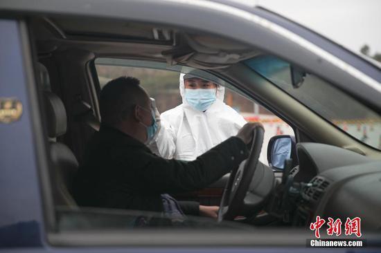 1月31日,在厦蓉高速贵阳东收费站出口,工作人员正在对车辆上的乘客进行体温检测,以防控新型冠状病毒感染的肺炎疫情。中新社记者 瞿宏伦 摄