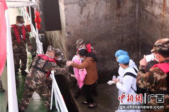 图为海警人员顺利将幼儿接到舰艇。刘寒丰  摄