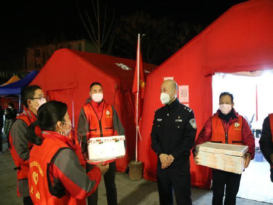 沈姐志愿者給卡點民警送夜宵。 屈鵬 攝