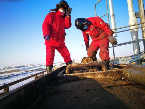 百口泉采油厂玛湖第二采油作业区员工李晓东正在现场巡检,确保油井正常生产。段晓霞 摄