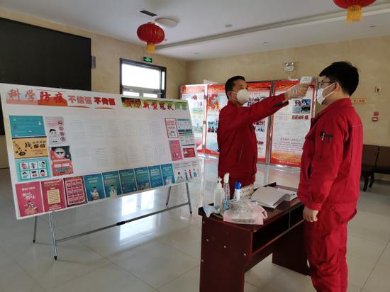2月5日,采氣一廠克拉美麗采氣作業區黨支部書記霍新春為每一位員工一日三次測量體溫。張丹