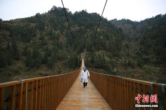 """今年50岁的苗族村医龙光庆,是贵州省黔东南苗族侗族自治州丹寨县排调镇双尧村的村医。多年来,他要服务双尧村四个自然寨的1300多苗族村民,是村民眼中的""""名医""""。新冠肺炎疫情发生后,龙光庆更加地忙碌,每天都要爬山涉水十多公里穿梭于河两岸的苗寨中,给村民们测量体温、宣传防控知识等。他说:""""作为一名村医,我就要尽自己的所能守护好村民的健康,这也是我学医以来一个最大的愿望。""""图为2月7日,龙光庆行走在前往排尧苗寨的铁索桥上。中新社发 黄晓海 摄"""