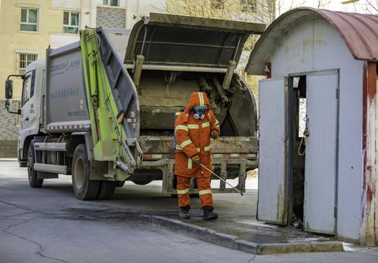 環衛工人正在對垃圾站進行消毒作業。李飛攝