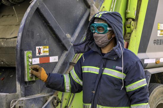 環衛工人正在裝載垃圾。李飛攝