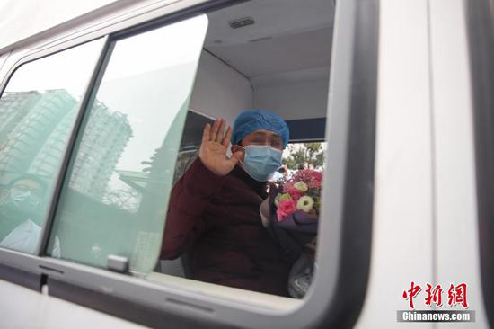 2月11日,贵阳,一名出院治愈者向医护人员挥手致意。当日,贵州省人民医院收治的4名新型冠状病毒感染的肺炎患者达到解除隔离治疗标准,同时出院。 中新社记者 瞿宏伦 摄