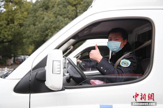 """2月12日,救护车驾驶员在出发时""""点赞""""。当日,贵州省派出12台救护车从贵阳出发,支援湖北鄂州新冠肺炎疫情防治工作。据悉,12台救护车分别从贵州贵阳、遵义等9市州的医疗机构选派,共有2台负压救护车,10台救护车。同时,救护车也运载了一批当地急需的医用设备和药品。 中新社记者 瞿宏伦 摄"""