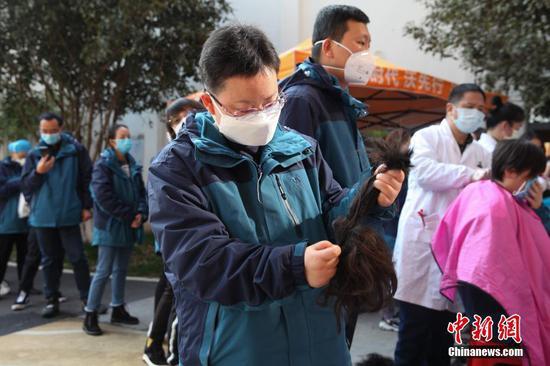 2月13日,为便于救治工作开展,贵州省第四批支援湖北鄂州医疗队首批完成培训的队员在进驻接管医院前集体理发。 中新社记者 石小杰 摄