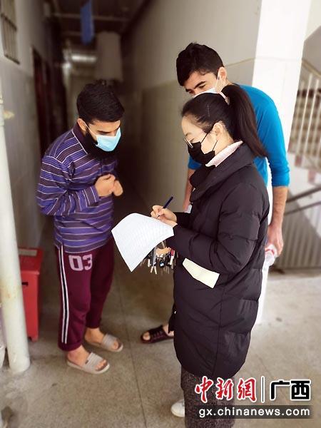 图为李汇哲给留学生测量体温。南师宣  摄