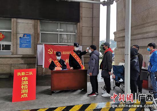 图为友谊关边检站民警在检测体温。