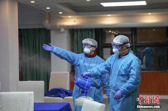 2名工作人员正在用消杀设备消毒。石小杰 摄