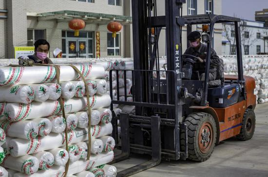 2月19日,在新疆巴音郭勒蒙古自治州尉犁县皓天农业科技开发有限公司,工人们正在转运农用地膜供应广大农户。李飞 摄
