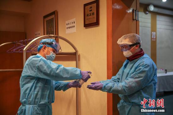 两名工作人员消毒作业完成后自我消毒。石小杰 摄