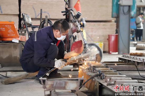 广西融水瑞森木业有限公司的厂房内,员工正在做复工前的设备检查工作。