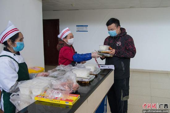 柳州铁道职业技术学院后勤工作人员、校医为同学们送饭。