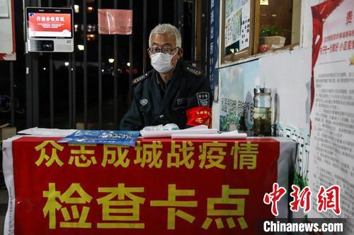 2月14日晚,贵阳花溪一小区工作人员在检查卡点坚守。 瞿宏伦 摄