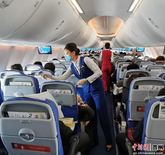 图为空乘人员为旅客检测体温。南航贵州公司供图