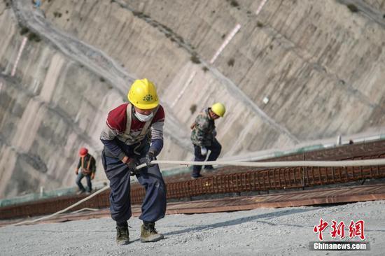 2月25日,工人正在施工。近日,壩址位于貴州省畢節市納雍縣的夾巖水利樞紐工程項目在做好疫情防控的同時有序復工,截至目前,項目復工工作面77個,占總工作面的32.6%。據悉,該工程是貴州省目前在建規模最大水利樞紐工程,大壩高154米、長429米,水庫正常蓄水位高程1323米,總庫容13.23億立方米。 中新社記者 瞿宏倫 攝