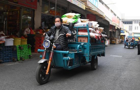 图为:一位工作人员在市场内运送货物。 王刚 摄