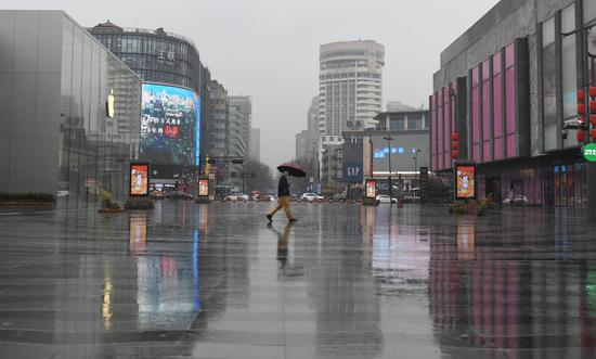 图为:一位市民撑伞走过湖滨路步行街。  王刚 摄