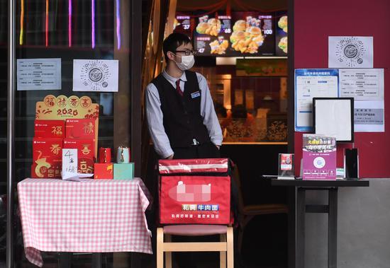 图为:一商家在店门外设立临时取餐点。 王刚 摄