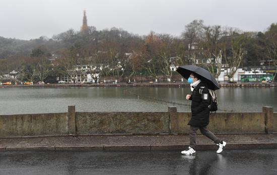 图为:一位游客戴口罩撑伞在断桥游览。  王刚 摄