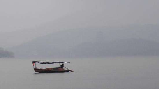 图为:一艘游船游弋在雷峰塔前。  王刚 摄