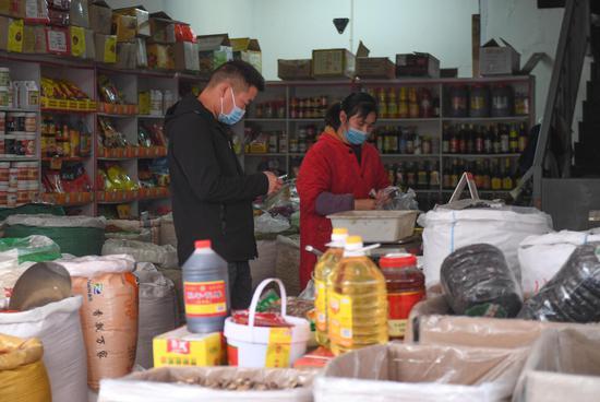 图为:一位市民在粮油店内购买。 王刚 摄