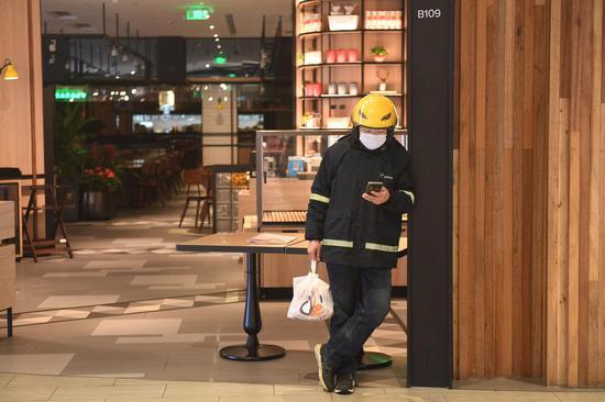 图为:一位外卖配送员在餐饮店门外等待外卖商品。 王刚 摄
