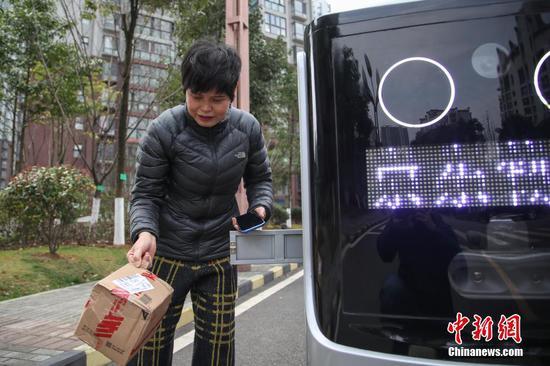 """2月26日,一位市民从配送机器人的快递箱中取走货物。京东物流日前在贵阳市观山湖区观山小区投用了智能配送机器人,实现了""""无接触送货""""。据悉,该配送机器人无人操控,能够自主规避障碍和往来的车辆、行人,并准确将货物送达目的地。 中新社记者 瞿宏伦 摄"""