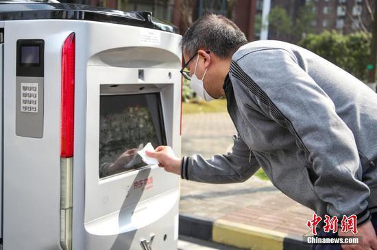 """2月26日,一位市民在配送机器人前输入验证码取件。京东物流日前在贵阳市观山湖区观山小区投用了智能配送机器人,实现了""""无接触送货""""。据悉,该配送机器人无人操控,能够自主规避障碍和往来的车辆、行人,并准确将货物送达目的地。 中新社记者 瞿宏伦 摄"""