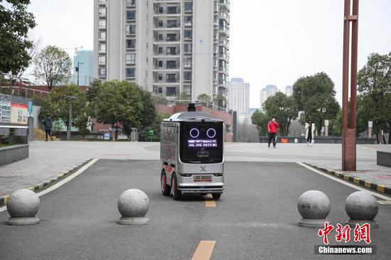"""2月26日,智能配送机器人在观山小区内送货。京东物流日前在贵阳市观山湖区观山小区投用了智能配送机器人,实现了""""无接触送货""""。据悉,该配送机器人无人操控,能够自主规避障碍和往来的车辆、行人,并准确将货物送达目的地。中新社记者 瞿宏伦 摄"""