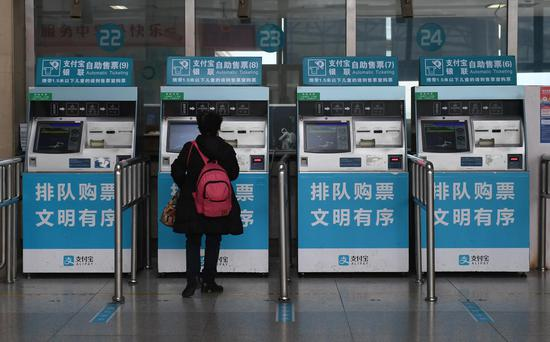 图为:一位旅客在准备购票。  王刚 摄