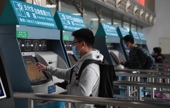 图为:多位旅客在自助购票。  王刚 摄