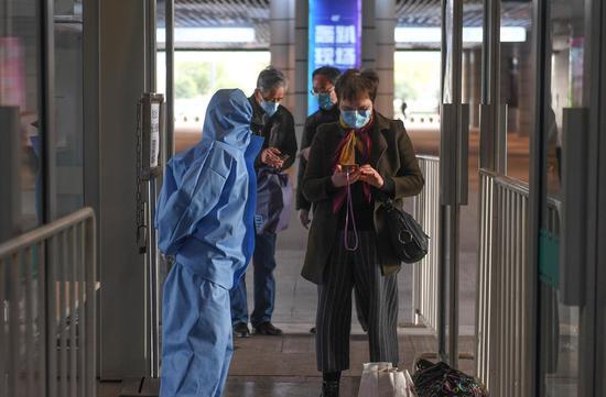 图为:两位旅客在进入杭州汽车客运中心站前接受健康码以及身份信息等查验。  王刚 摄