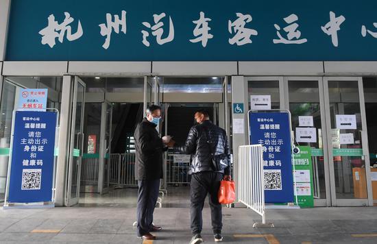 图为:一位旅客进入杭州汽车客运中心站前接受查验。  王刚 摄