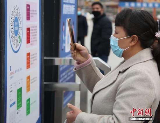 """3月1日,旅客在进站前扫描登记""""贵州健康码""""。近日,贵阳站站前广场上旅客逐渐增多。中新社记者 瞿宏伦 摄"""