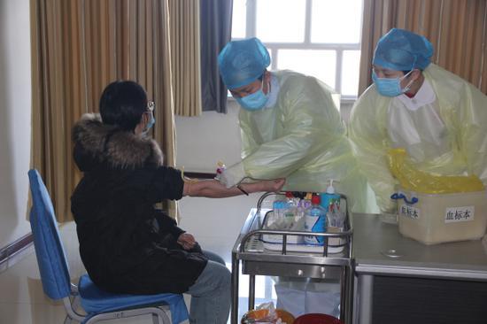 發熱門診醫務工作者為發熱患者抽血。