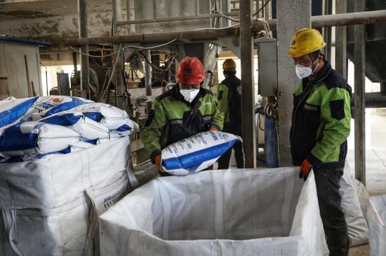 位于尉犁縣尉東礦產品加工園區內的鑫坤農業科技發展有限公司生產車間內,化肥生產的轉股裝置正在緊鑼密鼓的進行生產,工人們正在裝運化肥。 龐博 攝