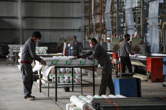 工人在尉犁縣皓天農業科技開發有限公司生產車間內包裝農用地膜。 龐博 攝