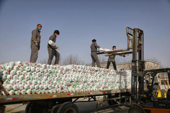 工人在尉犁縣皓天農業科技開發有限公司內裝運農用地膜。  龐博 攝