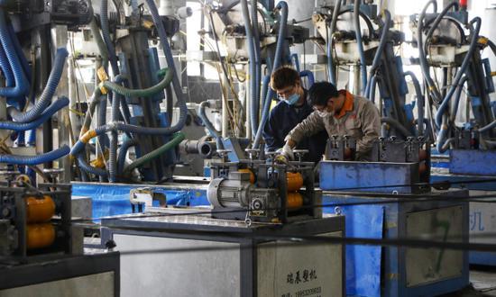 尉犁縣詠發塑業責任有限公司生產車間內機聲隆隆,工人們正按照嚴格操作規程和技術規范工作。 龐博 攝