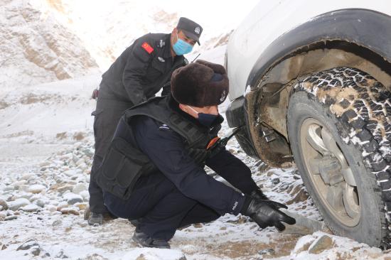 图为民警正在往轮胎下面铺垫石子。