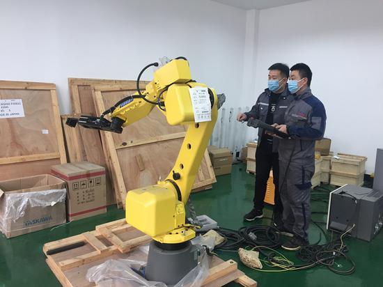 工作人员正在调试机器人。  项乐茹 摄