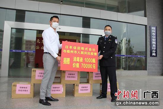 图为刘伟向抗疫一线警务工作人员捐赠消毒液。