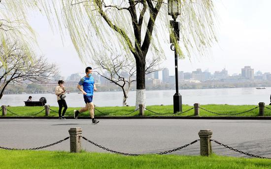 一位市民在白堤上跑步健身。  柱子(通讯员) 摄